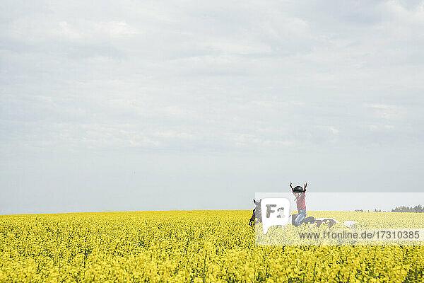 Sorgloses Mädchen reitet Pferd in sonnigen gelben Rapsfeld