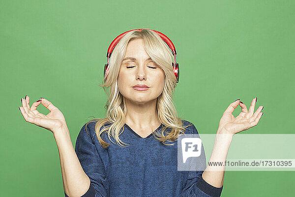 Porträt heitere Frau meditiert mit Kopfhörer