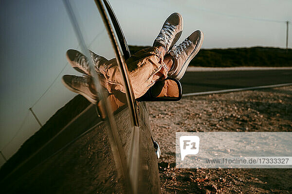 Woman relaxing legs on car window during sunset