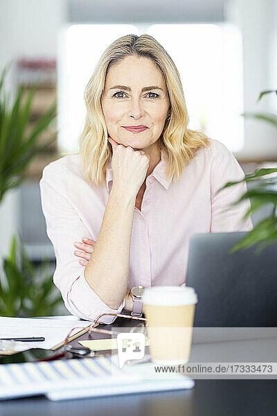 Weibliche Fachkraft mit Hand am Kinn am Schreibtisch im Heimbüro