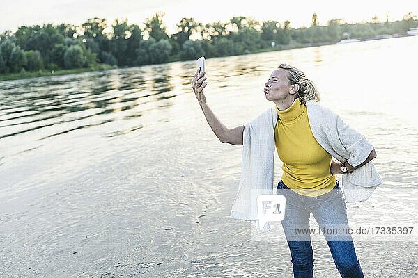 Woman puckering while taking selfie through smart phone at riverbank