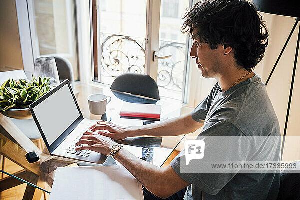 Mann benutzt Laptop bei der Arbeit von zu Hause aus
