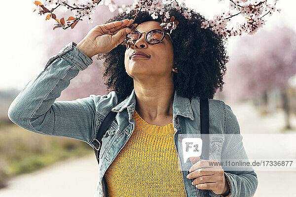 Woman with denim jacket smelling cherry flowers
