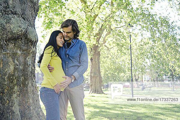 Frau umarmt ihren Mann vor einem Baumstamm im Park