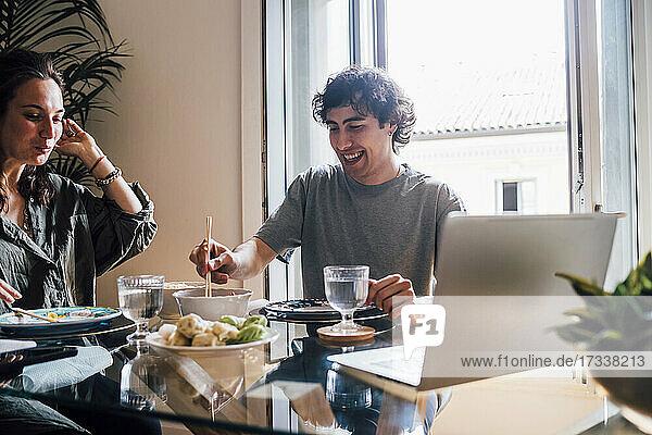Lächelnder Mann isst Essen  während er neben einer Frau zu Hause sitzt
