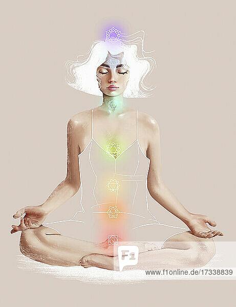 Die sieben Chakra-Symbole über einer meditierenden jungen Frau