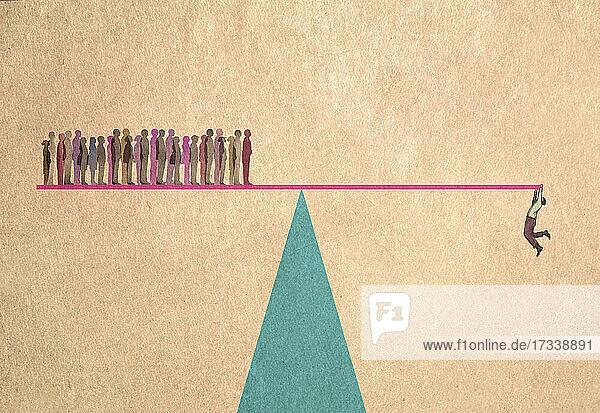 Viele Menschen auf einer Seite der Wippe und ein Mann hängt auf der anderen Seite