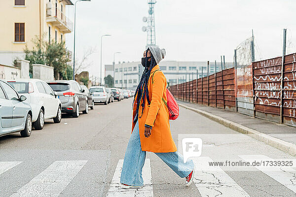 Italy  Milan  Woman in face mask crossing street