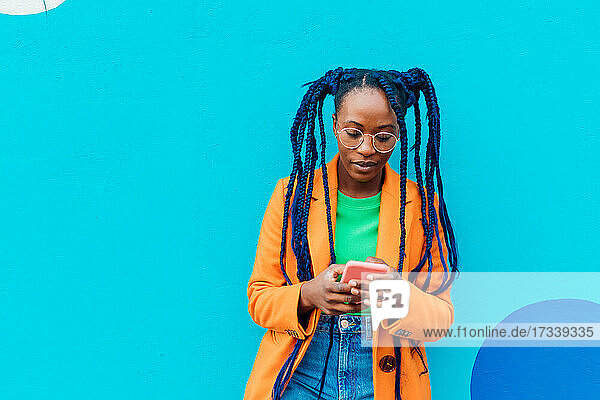 Italy  Milan  Woman with braids using smart phone against blue wall