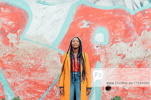 Italy  Milan  Portrait of woman with braids against graffiti covered wall