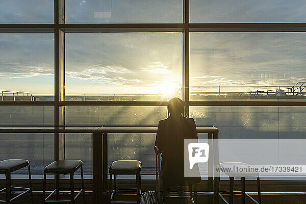 UK  London  Rear view of woman at airport terminal at sunset
