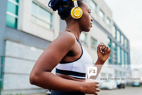 Italy  Milan  Woman with headphones jogging in city