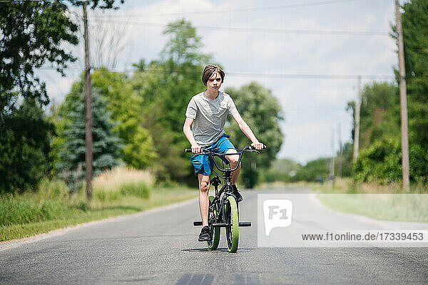 Canada  Ontario  Kingston  Boy (14-15) riding bicycle