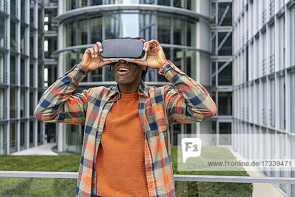 Germany  Berlin  Man using virtual reality goggles in city