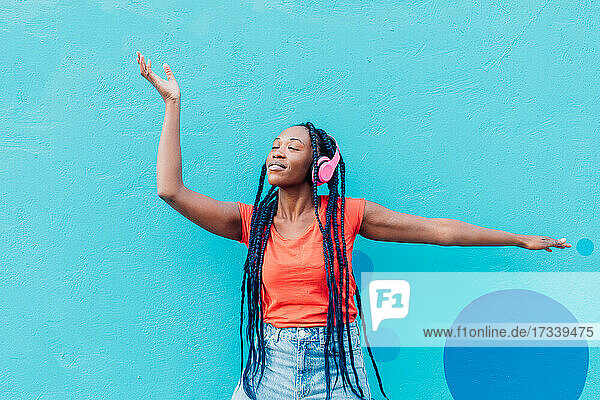 Italy  Milan  Young woman with headphones dancing in front of blue wall