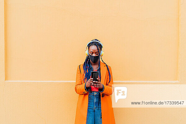 Italy  Milan  Woman in face mask with headphones and smart phone outdoors