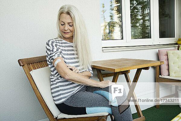 Austria  Vienna  Senior woman with adhesive bandage on arm sitting on porch