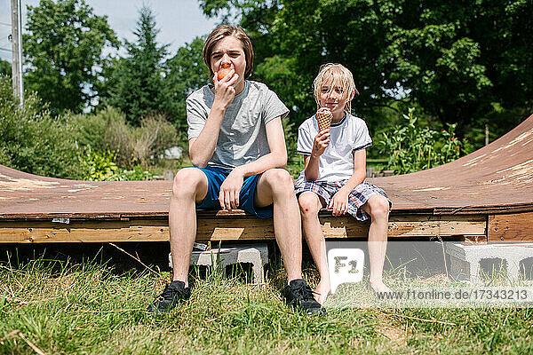 Canada  Ontario  Kingston  Boys (8-9  14-15) eating ice cream and apple