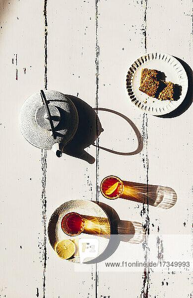Zwei Gläser Tee und Teller mit Crunchies auf Holzuntergrund