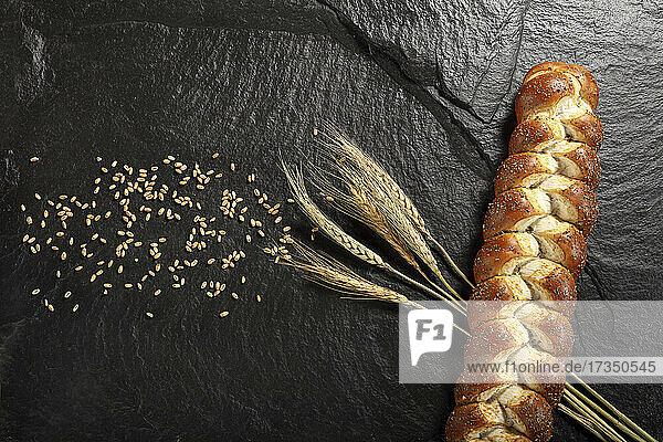 Hefezopf daneben Getreidekörner und Getreideähren