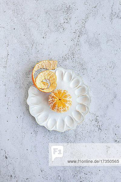 Geschälte Honeygold-Mandarine auf dekorativer Keramikplatte