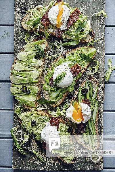 Gesunde 'grüne' Brote mit pochiertem Ei und krossem Speck