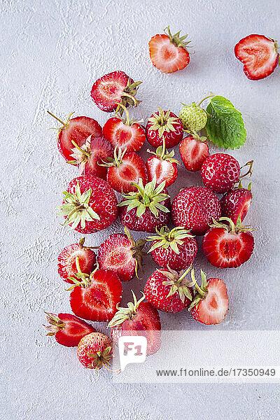 Frische Erdbeeren  teilweise halbiert auf hellem Untergrund