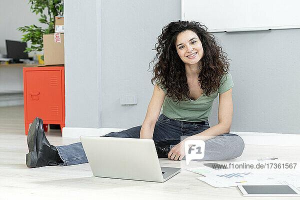 Lächelnde Frau mit Laptop sitzt mit Dokumenten auf dem Boden im Büro