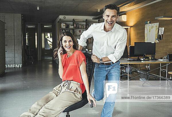 Fröhlicher Kollege  der eine Geschäftsfrau auf einem Bürostuhl sitzend dreht