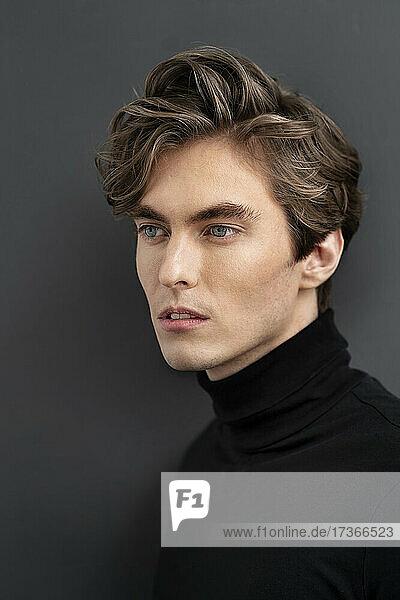 Gutaussehende männliche Fachkraft vor grauem Hintergrund