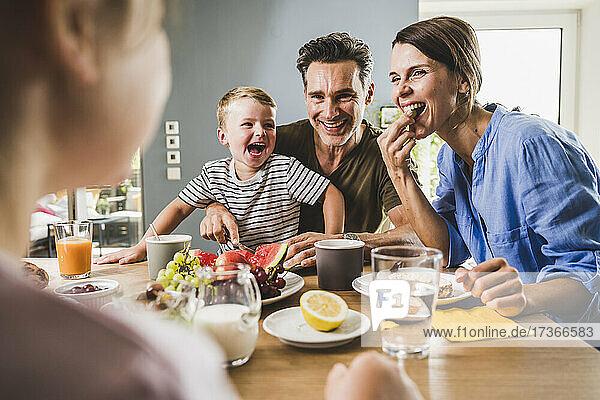 Vater und Mutter betrachten ihre Tochter beim Frühstück zu Hause