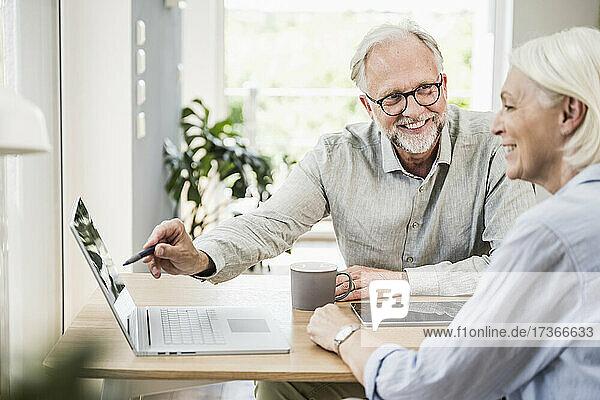 Lächelnder männlicher Berufstätiger  der auf einen Laptop zeigt  während er einer weiblichen Kollegin im Heimbüro etwas erklärt