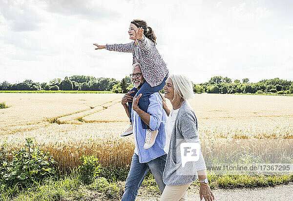 Grandparents walking with playful granddaughter during sunny day