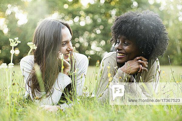 Porträt von lächelnden jungen Freundinnen  die im Park liegen