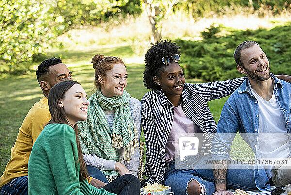 Glückliche junge Freunde sitzen zusammen in einem öffentlichen Park