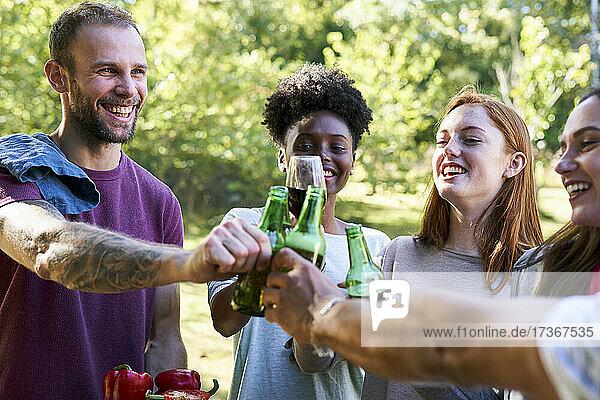 Glückliche junge Freunde stoßen im Garten mit Bierflaschen an