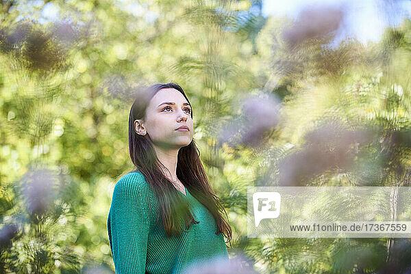 Nachdenkliche junge Frau im öffentlichen Park stehend Nachdenkliche junge Frau im öffentlichen Park stehend