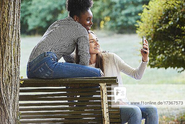 Lächelnde junge Freunde machen ein Selfie mit ihrem Smartphone in einem öffentlichen Park