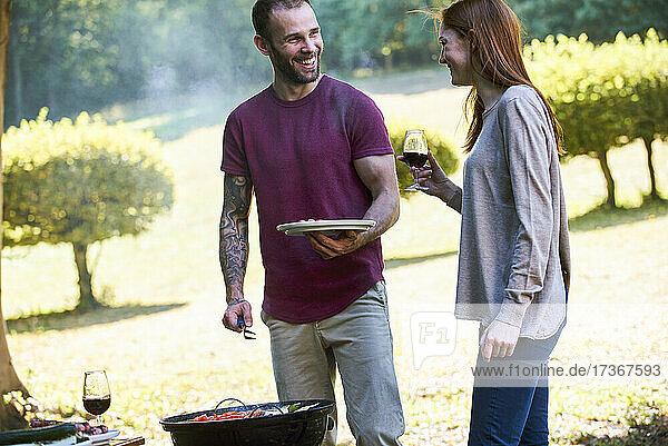 Lächelndes junges Paar  das sich in der Nähe eines Grillplatzes im Park unterhält
