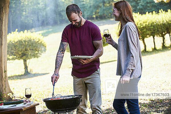Lächelndes junges Paar  das sich in der Nähe eines Grillplatzes im Park unterhält Lächelndes junges Paar, das sich in der Nähe eines Grillplatzes im Park unterhält