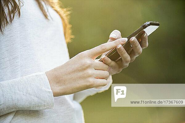 Mittelteil einer jungen Frau  die im Park ein Smartphone benutzt