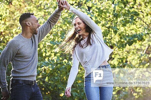 Lächelndes junges Paar tanzt im öffentlichen Park Lächelndes junges Paar tanzt im öffentlichen Park