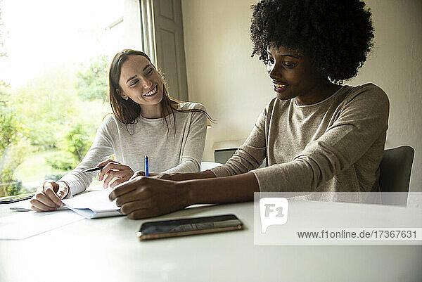 Lächelnde junge Freunde  die zu Hause gemeinsam Dokumente schreiben
