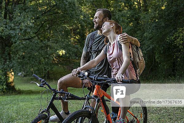 Lächelndes junges Paar sitzt auf Fahrrädern im Wald
