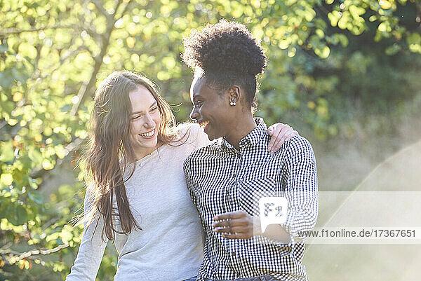 Lächelnde junge Freunde beim Spaziergang im öffentlichen Park Lächelnde junge Freunde beim Spaziergang im öffentlichen Park