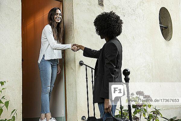 Lächelnde junge Freundinnen beim Händeschütteln vor der Haustür