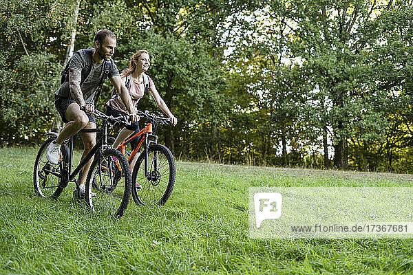 Junges Paar radelt im Wald