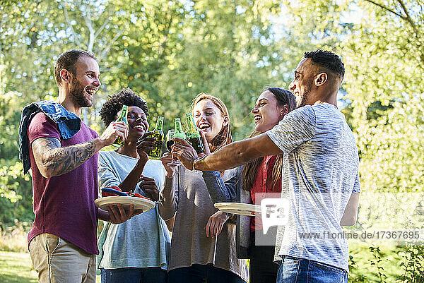 Fröhliche junge Freunde stoßen mit Getränken im Garten an