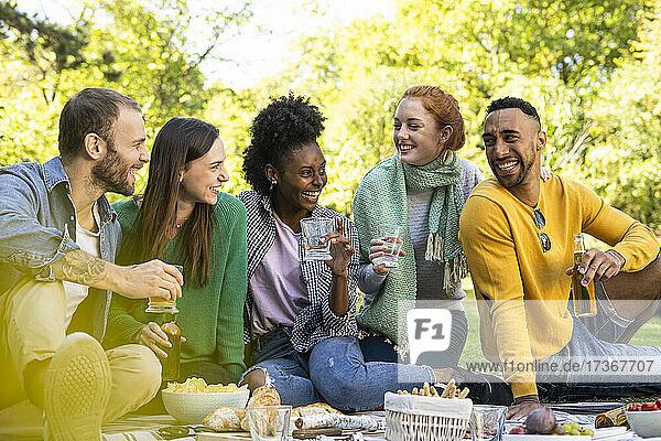 Lächelnde junge Freunde sitzen zusammen in einem öffentlichen Park