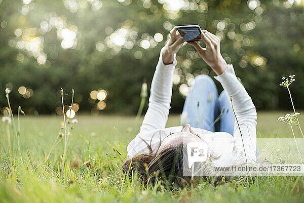 Junge Frau benutzt ihr Smartphone  während sie im Park liegt  Orgeval